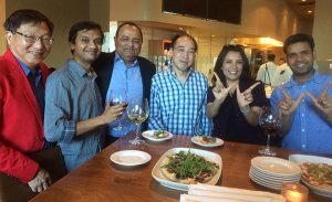 Dinner group of UW comp sci alumni making the W sign.