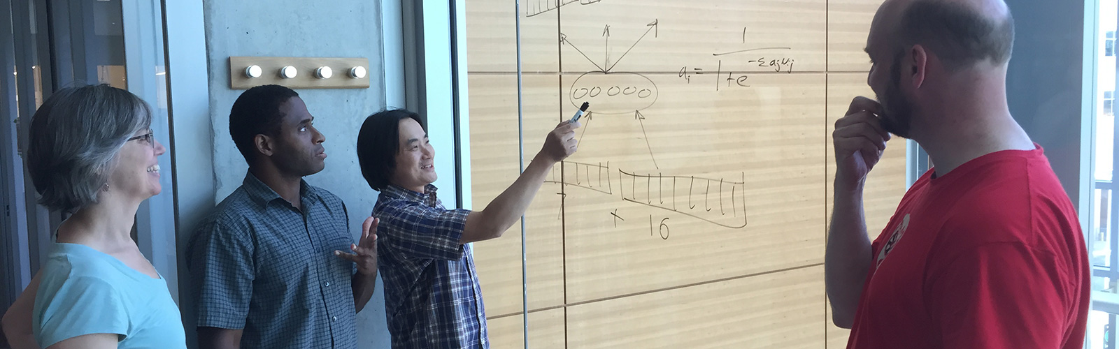 Researchers collaborate, aided by a diagram drawn on a window.