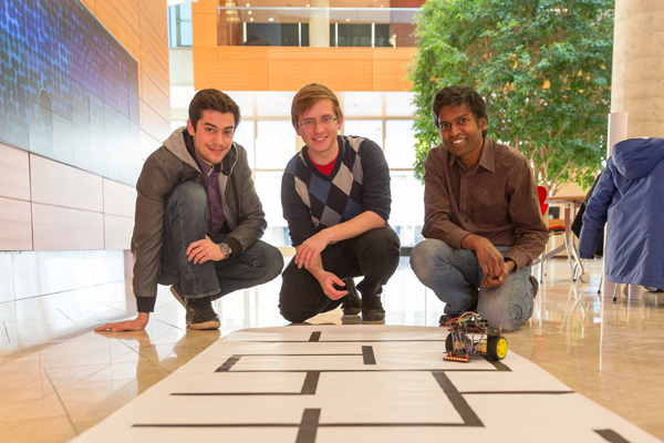 Three students kneel in front of a path for a programmable robot.
