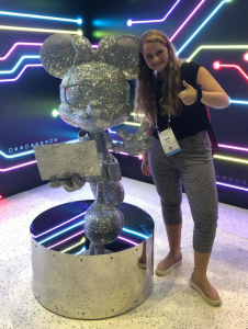 Emilie Rajka with sculpture of Minnie Mouse holding a laptop